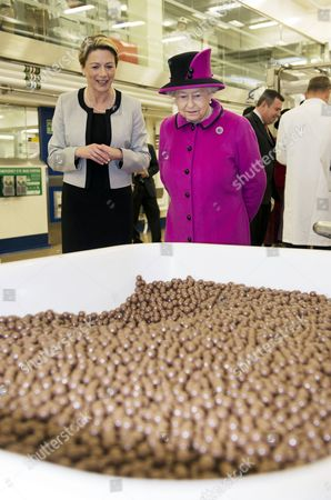 Fiona Dawson, President of Mars Chocolate UK shows Queen Elizabeth II a vat containing Maltesers chocolate sweets