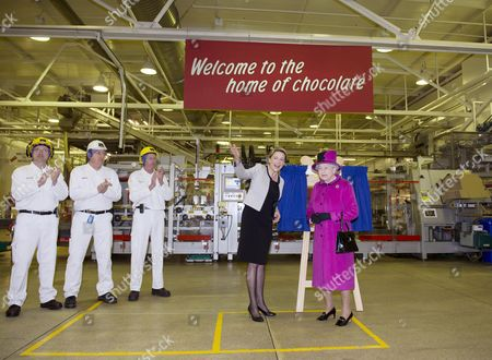 Stock Image of Fiona Dawson (C), President of Mars Chocolate UK stands alongside Queen Elizabeth II in the Maltesers packing line