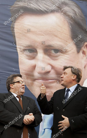Tom Watson and Ed Balls with giant poster of David Cameron