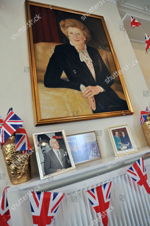 A painting depicting the late Prime Minister Margaret Thatcher hangs from the wall, alongside photographs of her with husband Denis Thatcher at the Conservative Party headquarters in Finchley