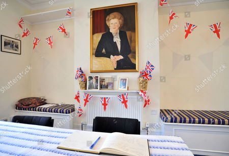 Stock Image of A painting depicting the late Prime Minister Margaret Thatcher hangs from the wall, alongside photographs of her with husband Denis Thatcher, at Conservative Party headquarters in Finchley