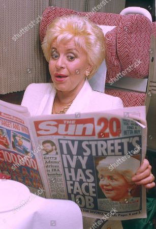 LYNNE PERRIE READING THE SUN NEWSPAPER