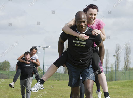 Stock Image of Daily Star Reporter Emma Brankin Gets Carried By Bb Winner Brian Belo On The Piggy Back Races At The 'no Carbs Before Marbs' Fitness Bootcamp At The Crowne Plaza Spa In Colchester.
