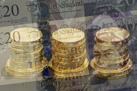 Three stacks of one pound and two pound coins seen through two twenty pound notes.