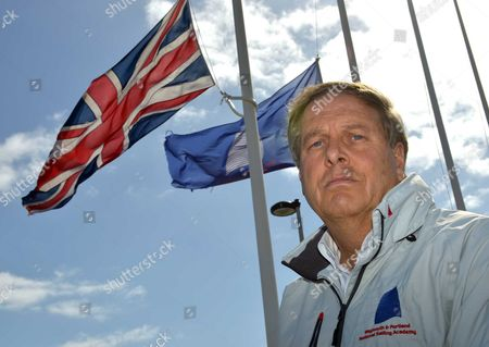 Academy Director John Tweed in front of the flags flying at half-mast