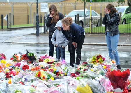 Woolwich residents fourteen years old Chloe Caulfield, 12 years old Emma Caulfield (L), their mother Nicola (C) and brother Ben lay some flowers near the entrance to Woolwich army barracks a short distance from the spot