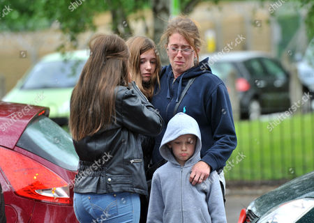 Woolwich residents fourteen years old Chloe Caulfield (L), 12 years old Emma Caulfield (C), their mother Nicola (R) and brother Ben lay some flowers near the entrance to Woolwich army barracks a short distance from the spot