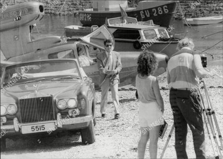 Tony Anholt Walks From A Flying Boat To A Rolls Royce Whilst Filming The Television Programme 'howards Way'.