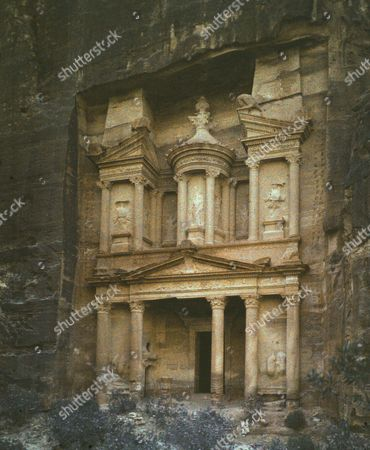 Stock Image of Petra, Jordan, rock-hewn capital of the Nabataens, c100 BC, 'A rose-red city half as old as Time'. The facade of the treasury. Early 20th century photograph. Archaeology