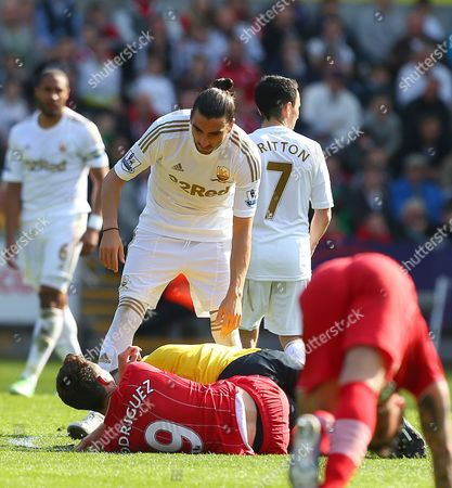 Referee Mark Halsey falls over Jay Rodriguez of Southampton before being helped to his feet by Chico Flores of Swansea City