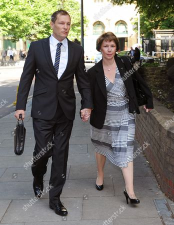 Stock Photo of Pc Simon Harwood 41 Arrives At Southwark Crown Court With This Wife Helen This Morning For The Second Day Of His Trial. Pc Harwood Is Accused Of Mr Tomlinson's Manslaughter During The G20 Demonstrations In April 2009 .