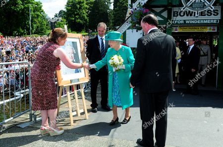 Queen Elizabeth II meets Linda Furniss and David Jackson of Keswick Tourist Association with their framed mosaic portrait as she arrives at Bowness on Windermere pier, Cumbria.