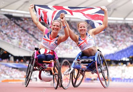Melissa Nicholls and Hannah Cockroft of Great Britain pose with the Union Jack flag after the 100m Women T33/34 Final