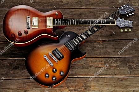 A Prs Se Bernie Marsden 53/10 Ltd (Top) And Gibson Les Paul Oo70s Tribute Electric Guitar On Wooden Floorboards