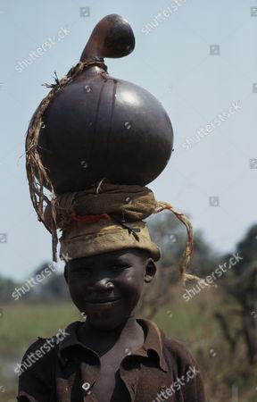 Portrait of Hutu child carrying water pot on head. Children Burundi