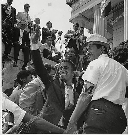 Actor Sammy Davis, Jr. waves to the crowd from the Lincoln Memorial