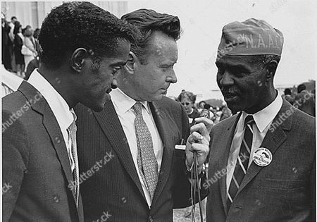 Sammy Davis, Jr., actor and performer, and Roy Wilkins, Executive Secretary of the National Association for the Advancement of Colored People are interviewed by a reporter, (C)