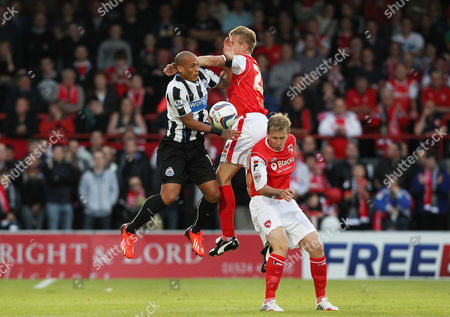 Yoan Gouffran of Newcastle United battles with Andy Parrish and Andrew Wright of Morecambe