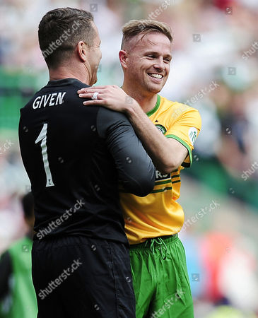 Goalkeeper Shay Given and former Westlife singer Nicky Byrne embrace after competing in a charity football match