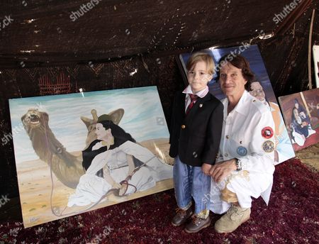 Spanish explorer Kitin Munoz with his son Prince Simeon Hassan pose in front of a painting, a portrait of Princess Kalina of Bulgaria