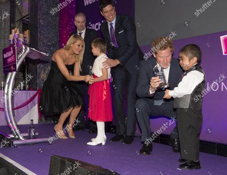Prince Harry presents an award to Jonathan He and Tess Daley presents an award to Maidison Kirk with Vernon Kay looking on