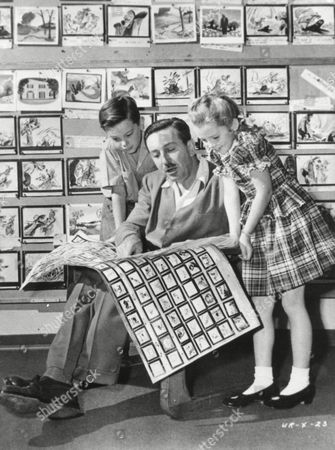 "December 27, 1946 - Walt Disney shows 2 young actors, Bobby Driscoll (left), and Luana Patten (right) the storyboards for his new production, ""Song of the South."""