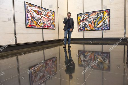 Dario Ballantini with his oil paintings titled Come Deve Andare and Qui Sotto
