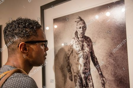 Visitor admires a photo of a man tattooed head to toe