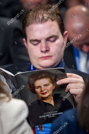 A Tory party member reads a Baroness Margaret Thatcher tribute