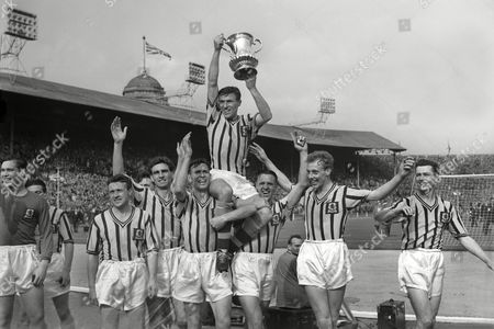 Football - 1957 FA Cup Final - Aston Villa 2 Manchester United 1 Aston Villa captain Johnny Dixon lifts the trophy on his teammates shoulders after victory at Wembley From left to right Leslie Smith Pat Saward Peter Aldis Dixon with trophy Stan Lynn Stan Crowther and Peter McParland FA Cup Final: Man Utd 2 Aston Villa 1