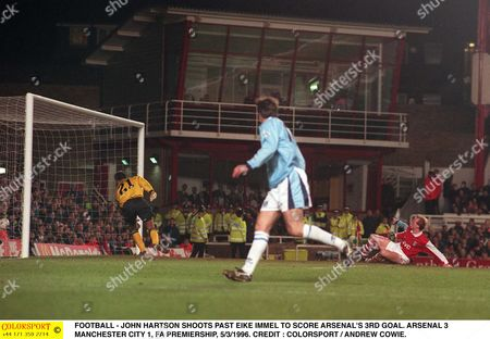 Stock Picture of FOOTBALL - JOHN HARTSON SHOOTS PAST EIKE IMMEL TO SCORE ARSENAL'S 3RD GOAL ARSENAL 3 MANCHESTER CITY 1 FA PREMIERSHIP 5/3/1996 Great Britain London