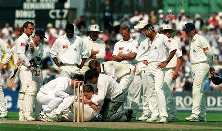 After being hit by ball from Devon Malcolm (England) Jonty Rhodes (South Africa) is helped up by medical staff as England players look on concerned England v South AFrica 3rd Test The Oval 18/08/1995 Great Britain London 3rd Test: England-SA