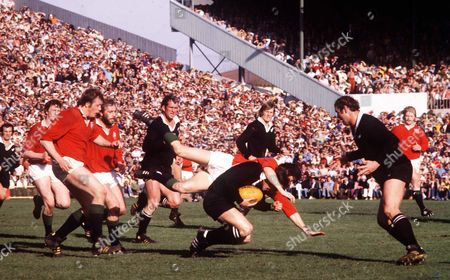Lyn Davis (New Zealand) gathers the ball as Andy Irvine (Lions) smothers him Andy Haden readies himself (right) New Zealand v British Lions 4th Test Auckland 13/08/1977 New Zealand Auckland 4th Test: NZ 10 Lions 9