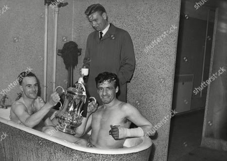 Football - 1955 FA Cup Final - Newcastle United 3 Manchester City 1 Newcastle's Ron Batty (right) and Ronnie Simpson celebrate in the bath with the trophy in the Wembley changing room Charlie Crowe (raincoat) missed the final through injury FA Cup Final: Newcastle 3 Man City 1