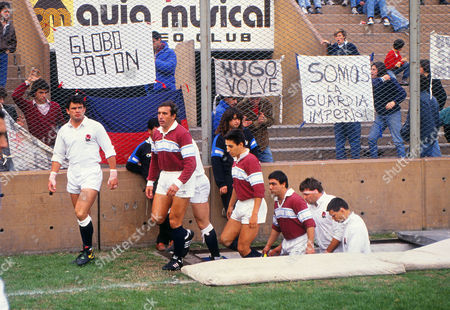 Rugby Union - 1990 England Tour of Argentina - Banco Nacion 29 England 21 Captains Will Carling and Hugo Porta lead out their teams at Buenos Aires with fans' banners behind on the fence Banco Nacio 29 England 21