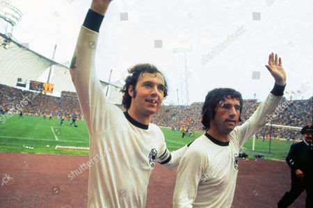 Football - 1974 World Cup Final - Netherlands 1 West Germany 2 West German captain Franz Beckenbauer left celebrates with teammate Gerd Muller after victory in the Olympiastadion Munich 1974WC Final: Holland 1 W Germany 2