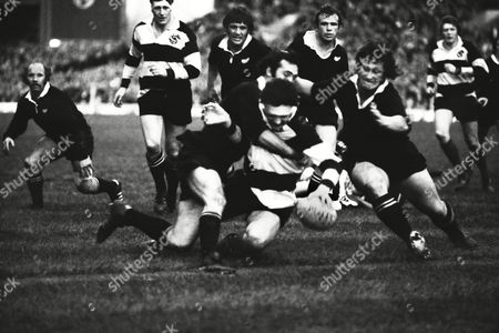 Stock Photo of Rugby Union - 1974 New Zealand Tour of British Isles - 'Final Challenge': Barbarians 13 New Zealand 13 Mervyn Davies of the Barbarians forces his way over the line for a try at Twickenham despite the tackles of New Zealand's Andy Leslie (left) and Kent Lambert Also pictured (left to right) is Sid Going (NZ) Willie John McBride (Barbarians) and Hamish MacDonald (NZ) [third in sequence] Barbarians 13 NZ 13