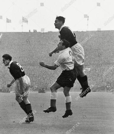 Football - 1952 / 1953 British Home Championship - England 2 Scotland 2 Scotland's Billy Liddell out-jumps England's Alf Ramsey at Wembley Scotland's Robert Johnstone (#8) is left 18/04/1953 England 2 Scotland 2