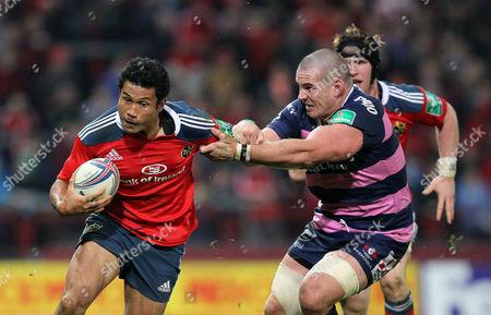 Munster's Casey Laulala fends off Dan Murphy of Gloucester