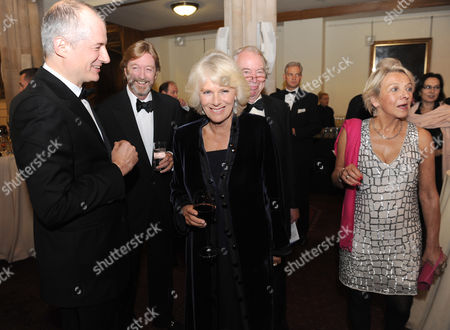 Stock Image of Camilla Duchess of Cornwall (centre) arrives for a reception with Emmanuel Roman, Chief Executive of Man Group PLC (left) Jon Aisbitt, Chairman Man Group PLC (second left) Jon Taylor, Chairman Booker Prize Foundation (second right) and Dotti Irving, Chief Executive of Four Colman Getty (right) ahead of the Man Booker Prize award ceremony