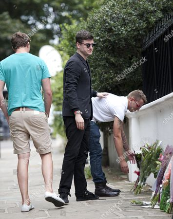 Actor James Alexandrou (black Suit) Who Played Martin Fowler In Eastenders Visits With Friends The Camden Home Of Singer Amy Winehouse Which Has Become A Shrine Of Tributes And Flowers Since The Singer Was Found Dead Last Friday.