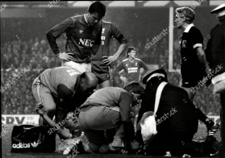 Everton V Liverpool Showing Physio's Attending To Jim Beglin After The Liverpool Full Back Broke His Leg Looking On Is Graeme Sharp.