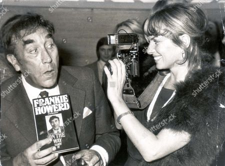 Actor / Comedian Frankie Howerd And Actress Julie Ege. Frankie Howerd Is Holding His Autobiography 'frankie Howerd - On The Way I Lost It' As Julie Ege Takes A Photograph. Pkt2076 - 143787.
