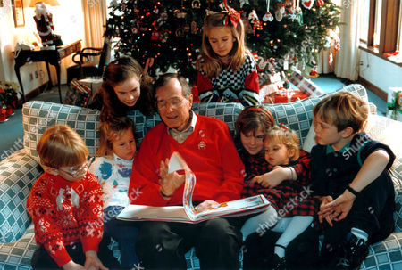 President George H Bush reading a Christmas story to his grandchildren, Pierce Bush, Marshall Bush, Barbara Bush, Lauren Bush, Jenna Bush, Ashley Bush and Sam LeBlond at Camp David, MD. Barbara and Jenna are the twin daughters of George W Bush, America