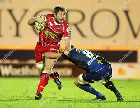 Richard Kelly of Scarlets is tackled by Leuan Jones of Newport Gwent Dragons