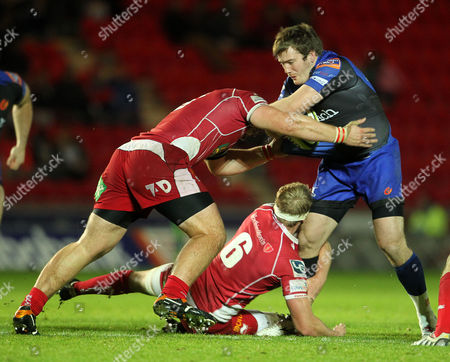 Hugh Gustafson is tackled by Richard Kelly and Craig Price