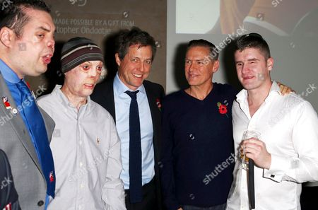 Stock Picture of Hugh Grant and Bryan Adams with veterans