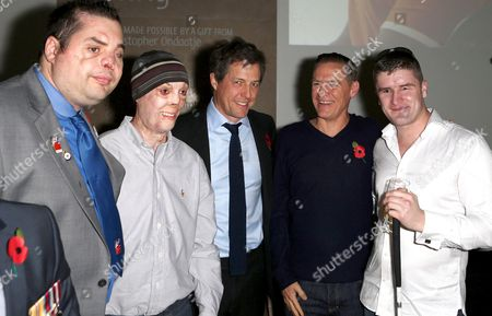 Stock Photo of Hugh Grant and Bryan Adams with veterans