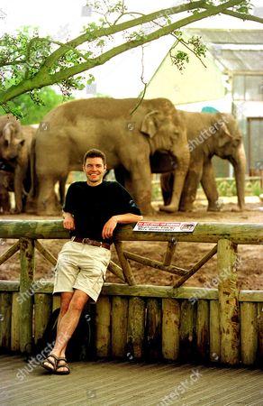 SOME ELEPHANTS PASS BEHIND VET STEVE LEONARD WHO WILL BE PRESENTING A NEW BBC SERIES ON PREDATORS
