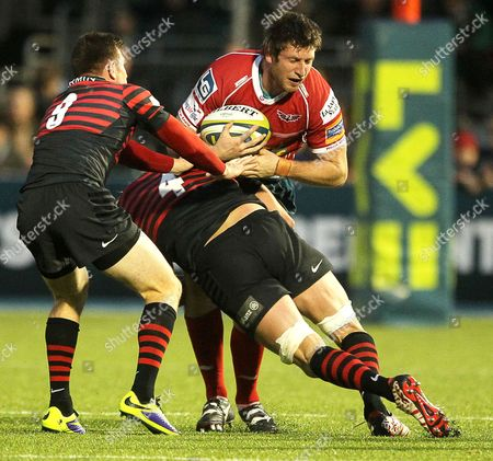 Richard Kelly of Scarlets is tackled by Ben Spencer and Alistair Hargreaves of Saracens